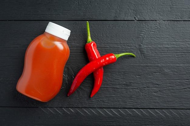 Chilisauce in flasche und paprika auf dunkler holzoberfläche