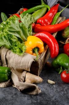 Chilischoten mischen sich mit salatblatt in einem holzkorb.