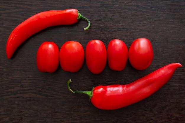 Chilischoten und tomaten auf einem dunklen hölzernen hintergrund