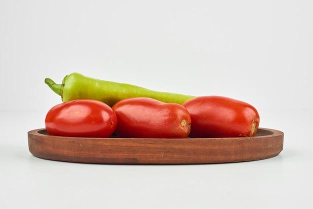 Chilischoten und tomaten auf einem holzbrett auf dem weiß.