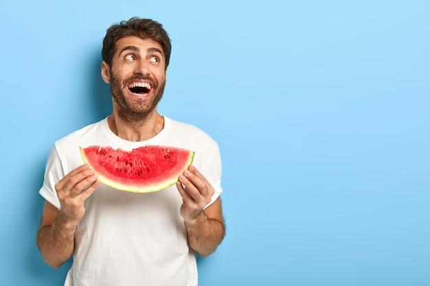 Chillender fröhlicher mann an einem sommertag, der eine scheibe wassermelone hält