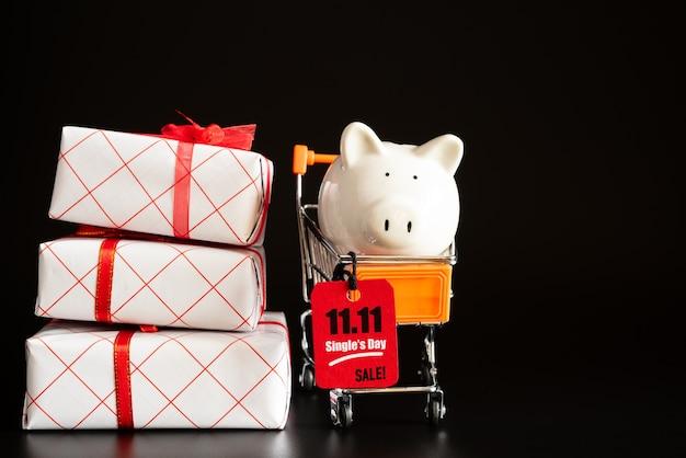 China, einzelverkaufstag 11.11, roter kartenumbau, der am minieinkaufswagen mit sparschwein hängt