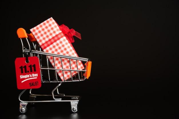 China, einzelverkaufstag 11.11, roter kartenumbau, der am minikaufwarenkorb mit geschenkboxen hängt