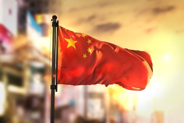 China-flagge gegen stadt verschwommen hintergrund bei sonnenaufgang hintergrundbeleuchtung