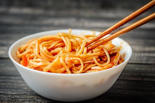 Chineese wok udon mit huhn auf dunklem hintergrund