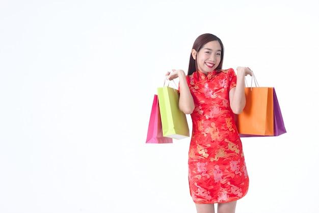 Chinesin, die rote kleidergriffeinkaufstasche cheongsam trägt glückliches fraueneinkaufskonzept.