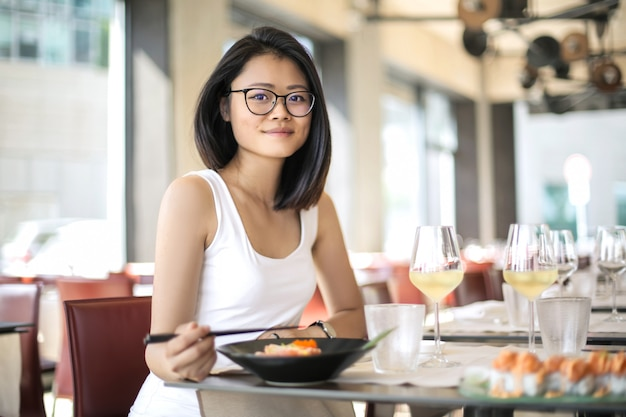 Chinesin, die sushi in einem restaurant isst