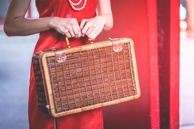 Chinesin hält einen hölzernen koffer für orientalisches reisekonzept der weinlese