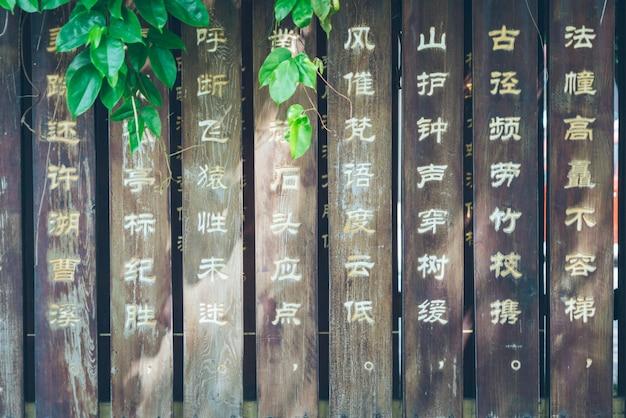 Chinesische alte gedichte auf den planken des parks geschnitzt, grüne pflanzen