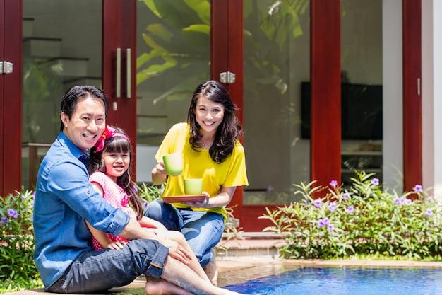 Chinesische familie am pool vor dem haus
