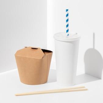 Chinesische fast-food-verpackung mit hohem winkel, leerer tasse und essstäbchen
