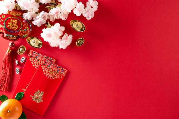 Chinesische festivaldekorationen des neuen jahres pow oder rotes paket, orangen- und goldbarren oder goldener klumpen auf rot