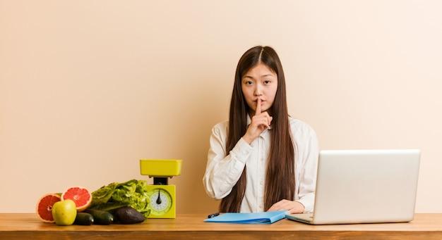 Chinesische frau der jungen ernährungswissenschaftlerin, die mit ihrem laptop arbeitet, der ein geheimnis hält
