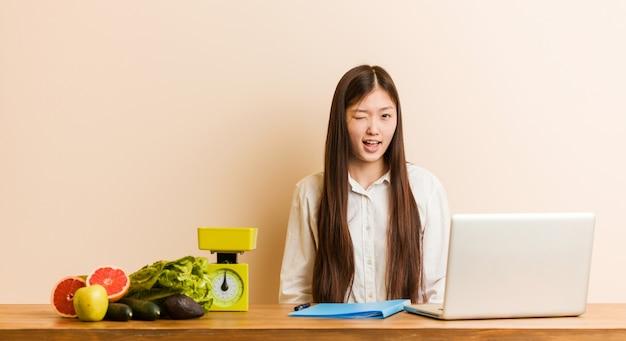 Chinesische frau des jungen ernährungswissenschaftlers, die mit ihrem laptop blinzelt, lustig, freundlich und sorglos arbeitet.