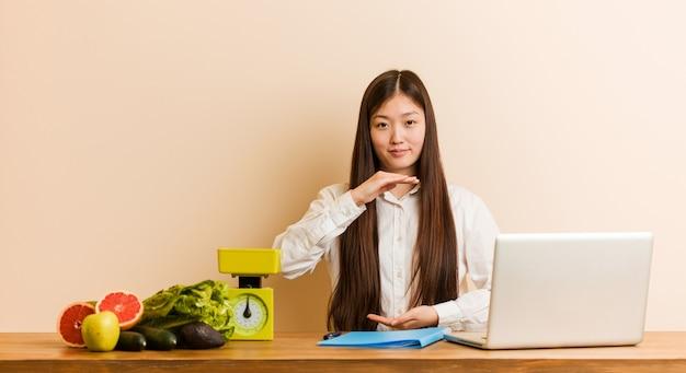 Chinesische frau des jungen ernährungswissenschaftlers, die mit ihrem laptop hält etwas mit beiden händen, produktdarstellung arbeitet.