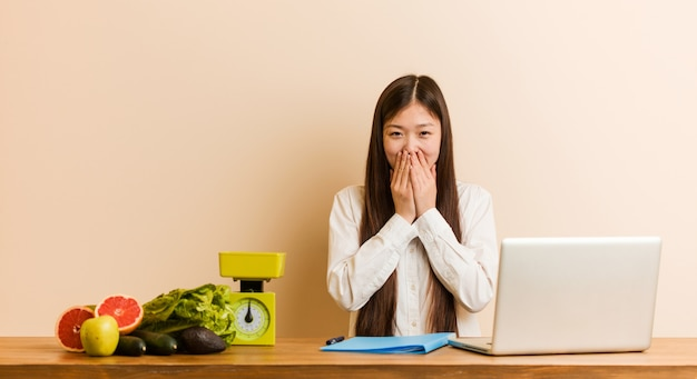 Chinesische frau des jungen ernährungswissenschaftlers, die mit ihrem laptop lacht über etwas, mund mit den händen bedeckend arbeitet.