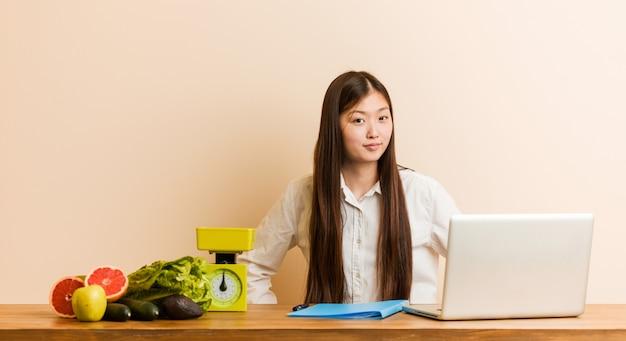 Chinesische frau des jungen ernährungswissenschaftlers, die mit ihrem laptop schilt jemand arbeitet, das sehr verärgert ist.