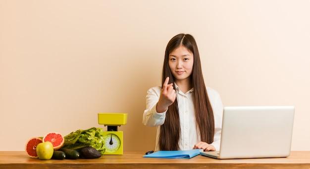 Chinesische frau des jungen ernährungswissenschaftlers, die mit ihrem laptop zeigt mit dem finger auf sie arbeitet, als ob einladung näher kommen.