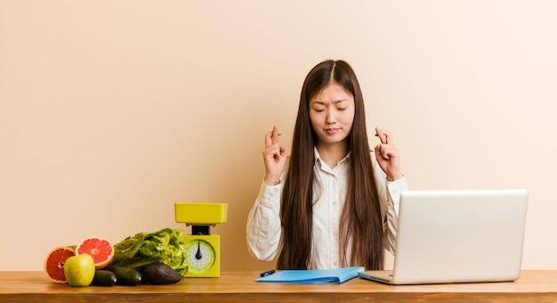 Chinesische frau des jungen ernährungswissenschaftlers, die mit ihren laptopüberfahrtfingern für das haben des glücks arbeitet