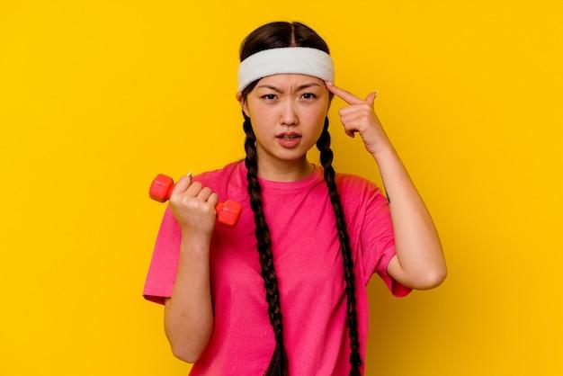 Chinesische frau des jungen sports lokalisiert auf gelb, das eine enttäuschungsgeste mit zeigefinger zeigt.