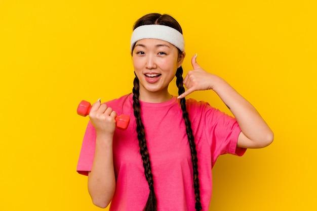 Chinesische frau des jungen sports lokalisiert auf gelber wand, die eine handy-anrufgeste mit den fingern zeigt.