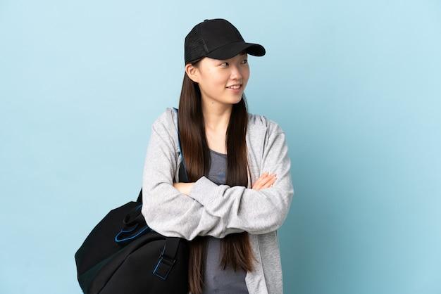 Chinesische frau des jungen sports mit sporttasche über der isolierten blauen wand, die beim lächeln nach oben schaut