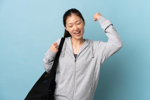 Chinesische frau des jungen sports mit sporttasche über isoliertem blau, das einen sieg feiert