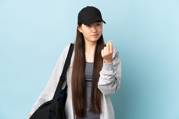 Chinesische frau des jungen sports mit sporttasche über isoliertem blau, das geldgeste macht