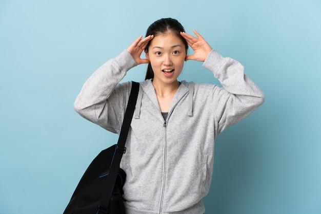 Chinesische frau des jungen sports mit sporttasche über isoliertem blau mit überraschungsausdruck
