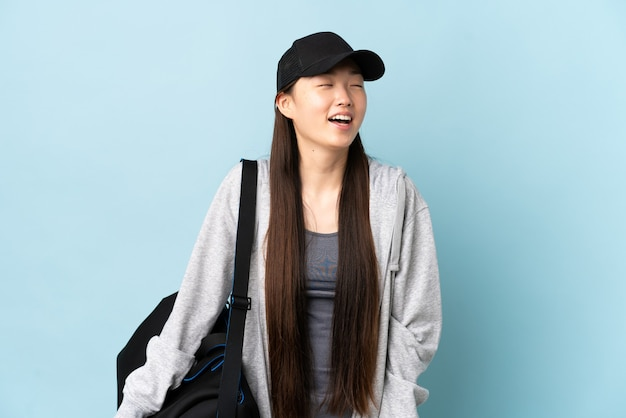Chinesische frau des jungen sports mit sporttasche über isoliertem blauem hintergrund lachend