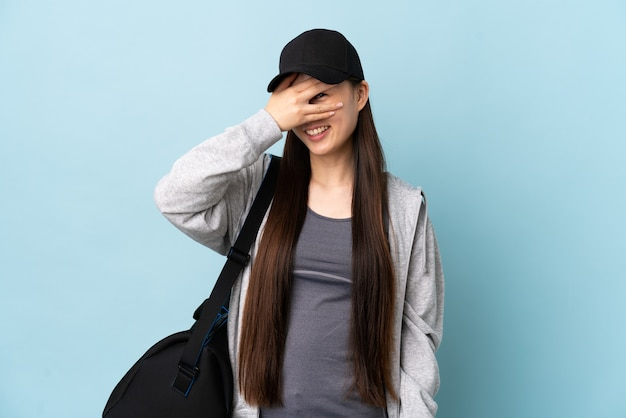 Chinesische frau des jungen sports mit sporttasche über isolierten blauen bedeckenden augen durch hände und lächeln