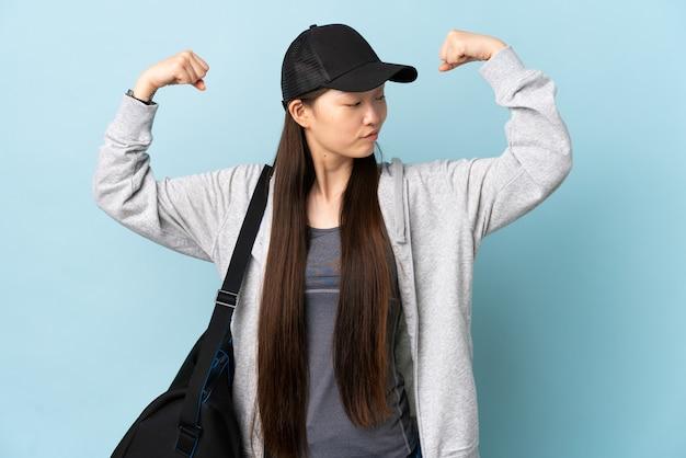Chinesische frau des jungen sports mit sporttasche über isolierter blauer wand, die starke geste tut