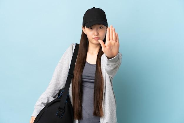 Chinesische frau des jungen sports mit sporttasche über isolierter blauer wand, die stoppgeste macht