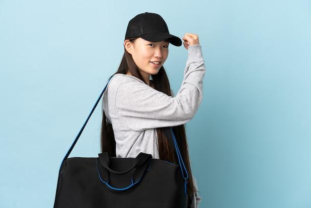 Chinesische frau des jungen sports mit sporttasche über lokalisiertem blauem hintergrund, der starke geste tut