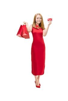 Chinesische frau des porträts mit dem cheongsam kleid, das rote papiertüten hält und kreditkarte zeigt