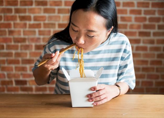 Chinesische frau, die chow mein isst