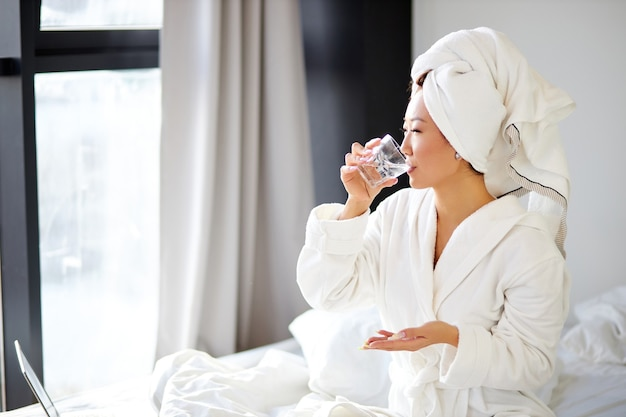 Chinesische frau, die eine pille nimmt, auf ihrem bett zu hause sitzt, bademantel und handtuch trägt, medikamente oder vitamine und glas wasser hält