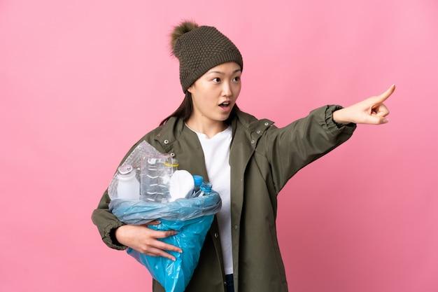 Chinesische frau, die eine tasche voll plastikflaschen hält, um über isolierte rosa wand zu recyceln, die weg zeigt