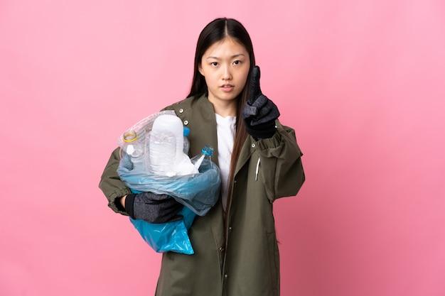 Chinesische frau, die eine tasche voller plastikflaschen hält, um über isolierte rosa wand zu recyceln, die eine mit ernstem ausdruck zählt