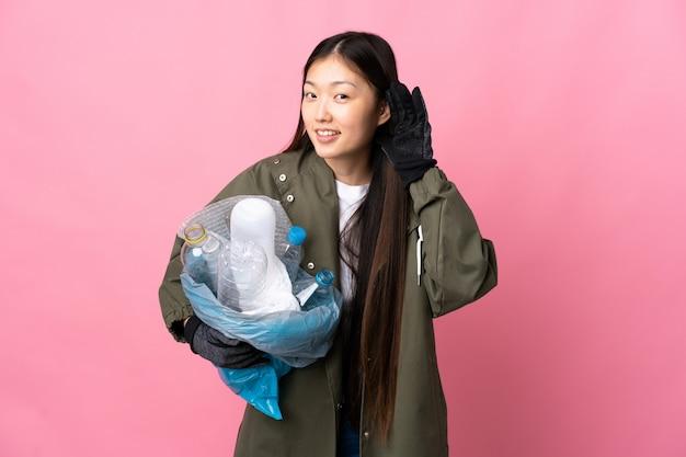 Chinesische frau, die eine tasche voller plastikflaschen hält, um über isolierte rosa wand zu recyceln, die etwas hört, indem man hand auf das ohr legt