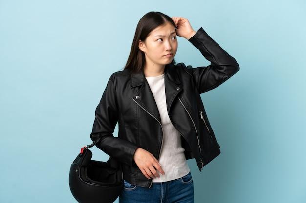 Chinesische frau, die einen motorradhelm über der blauen wand hält, die zweifel und mit verwirrendem gesichtsausdruck hat