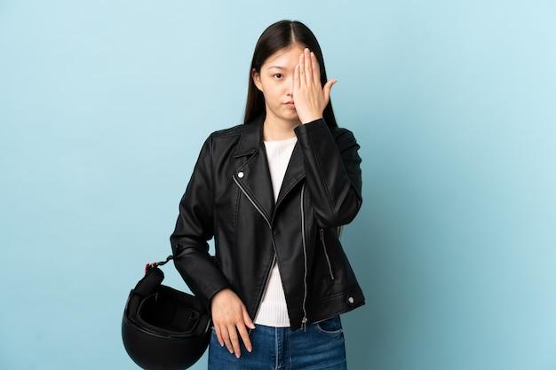 Chinesische frau, die einen motorradhelm über isolierter blauer wand hält, die ein auge von hand bedeckt