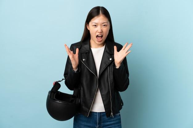 Chinesische frau, die einen motorradhelm über isolierter blauer wand hält, unglücklich und frustriert mit etwas