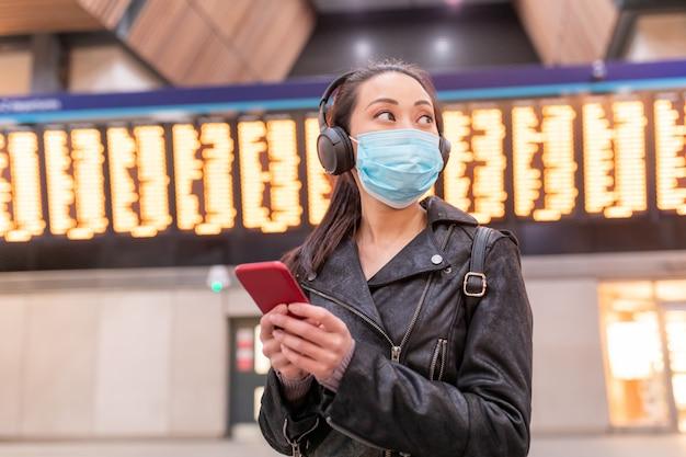 Chinesische frau, die gesichtsmaske am bahnhof trägt und soziale distanz beibehält - junge asiatische frau, die smartphone benutzt und weg mit abflugankunftstafel dahinter schaut - gesundheits- und reisekonzepte