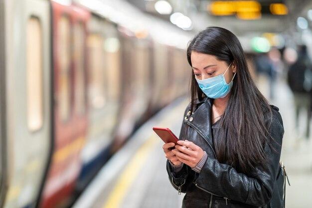 Chinesische frau, die gesichtsmaske am u-bahnhof trägt und soziale distanz hält - junge asiatische frau, die auf den zug wartet und ein smartphone hält - gesundheits- und reisekonzepte