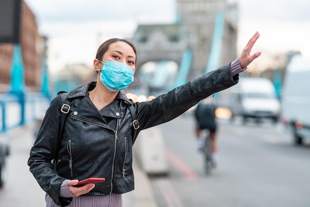 Chinesische frau in london, die gesichtsmaske trägt und ein taxi anruft - junge asiatische frau neben belebter straße in der stadt, die ein smartphone benutzt, um eine fahrt zu buchen - gesundheits- und lebensstilkonzepte