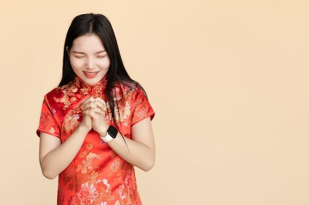 Chinesische frauen, die traditionelles qipao-tuch anziehen machen sie einen wunsch oder beten sie beim chinesischen neujahrsfest mit kopierraum.
