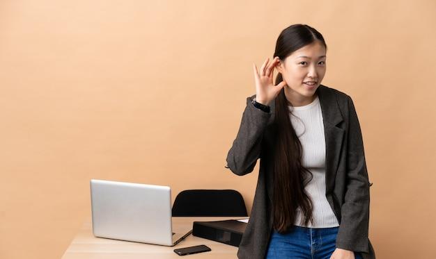 Chinesische geschäftsfrau an ihrem arbeitsplatz, der etwas hört, indem man hand auf das ohr legt