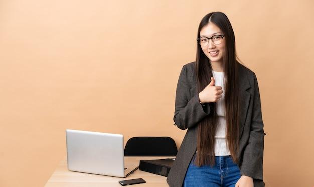 Chinesische geschäftsfrau an ihrem arbeitsplatz, die eine daumen hoch geste gibt