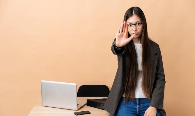 Chinesische geschäftsfrau an ihrem arbeitsplatz, die stoppgeste macht